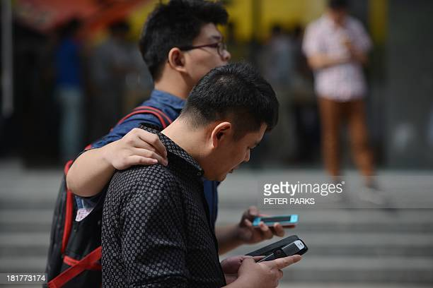A couple use their mobile devices on a street in Shanghai on September 25 2013 China will open its first free trade zone in an ambitious effort to...