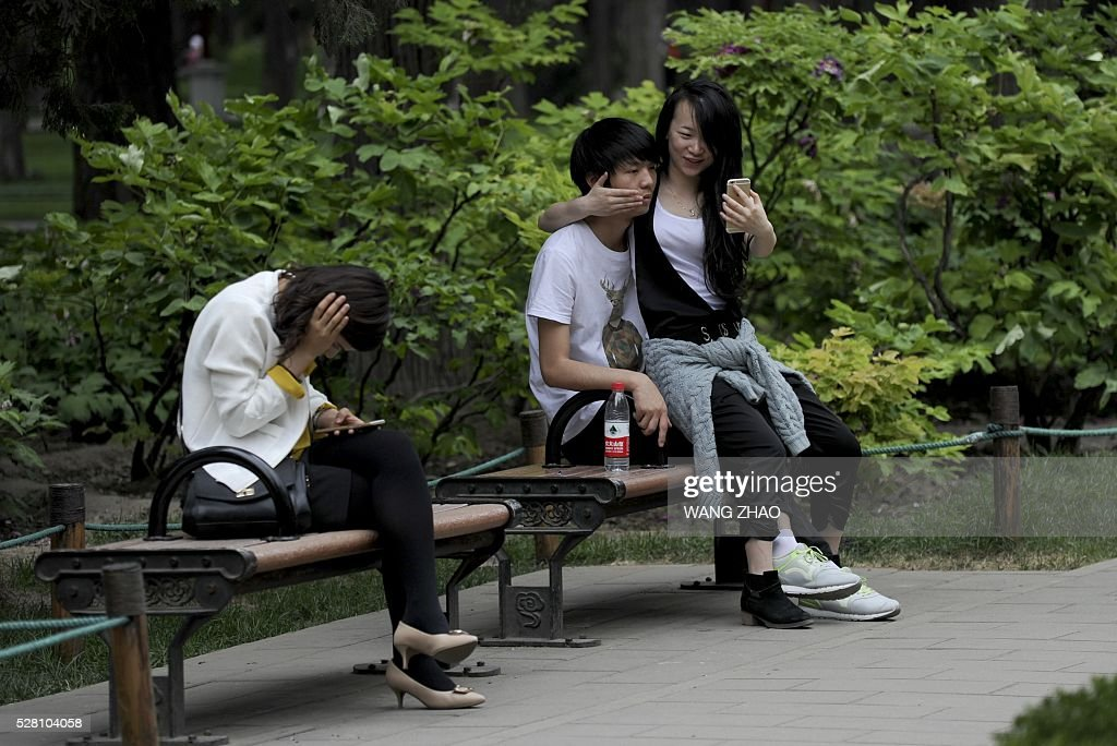A couple uses a mobile phone to take a picture at a park in Beijing on May 4, 2016. / AFP / WANG