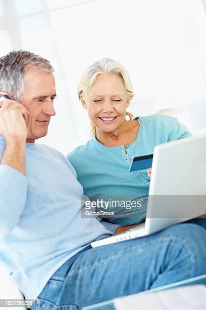 Couple à l'aide d'un téléphone portable et de carte de crédit pour acheter en ligne