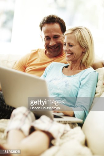 A couple using a laptop on a couch. : Stock Photo