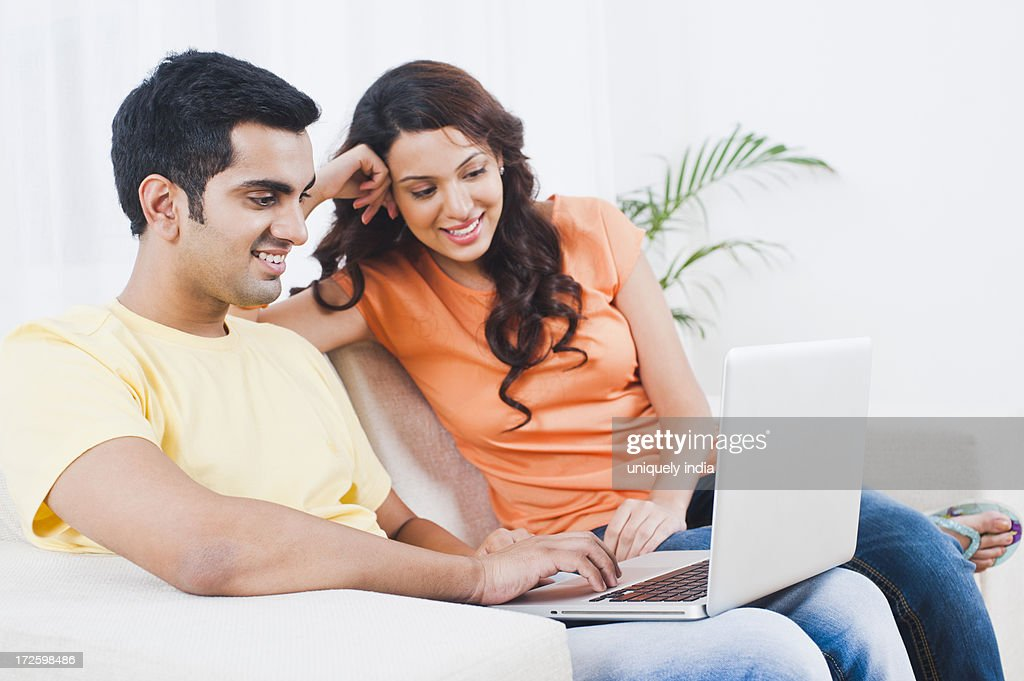 Couple using a laptop on a couch : Stock Photo