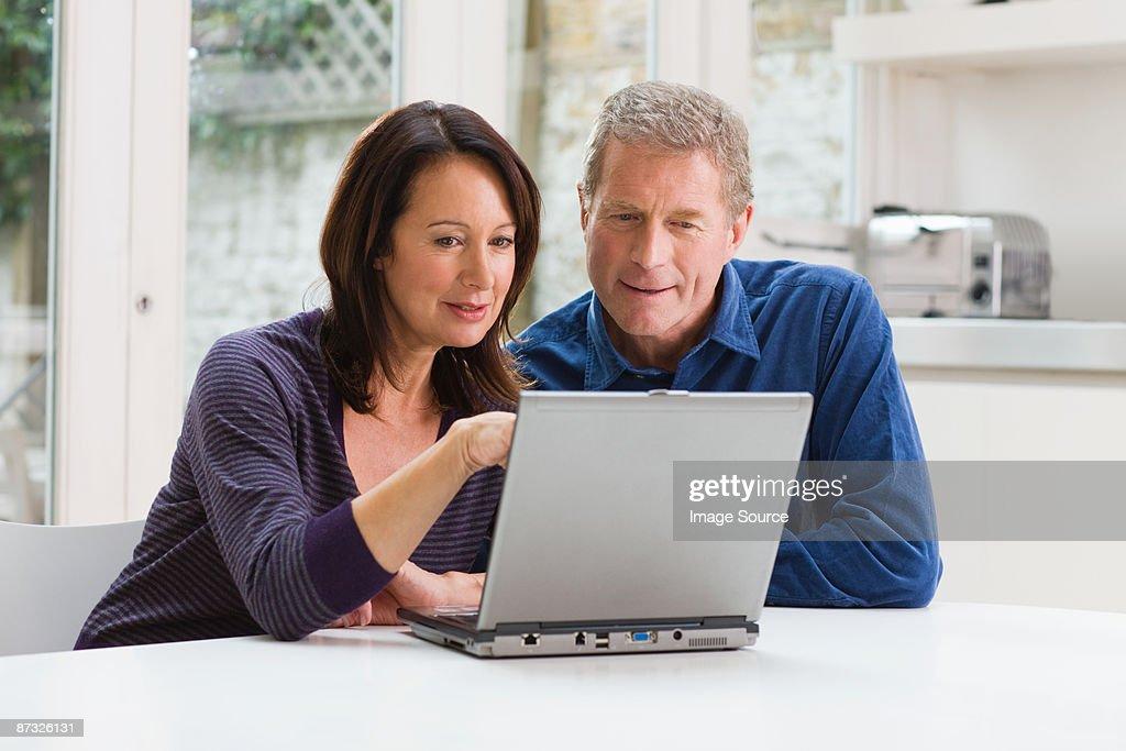 A couple using a laptop : Stock Photo