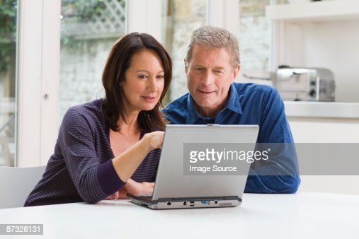 A couple using a laptop : Stock Photo