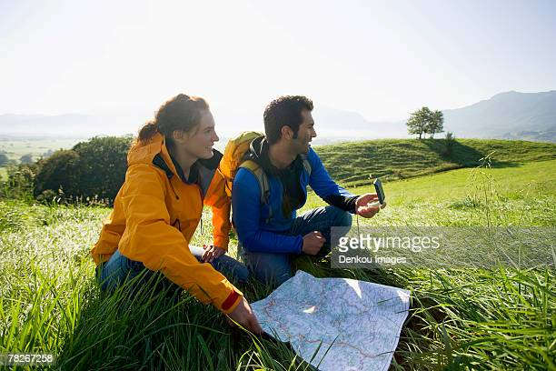 A couple using a map and a compass to find directions.