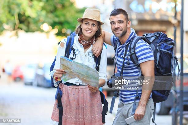 Couple using a map on street