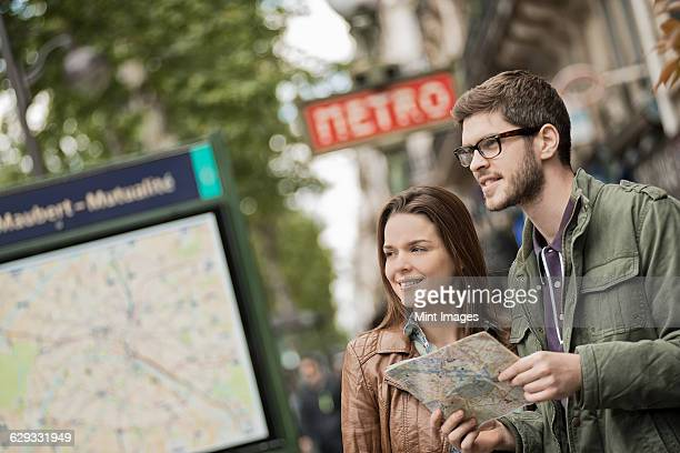 A couple using a street map beside an information sign under a metro sign in a city.