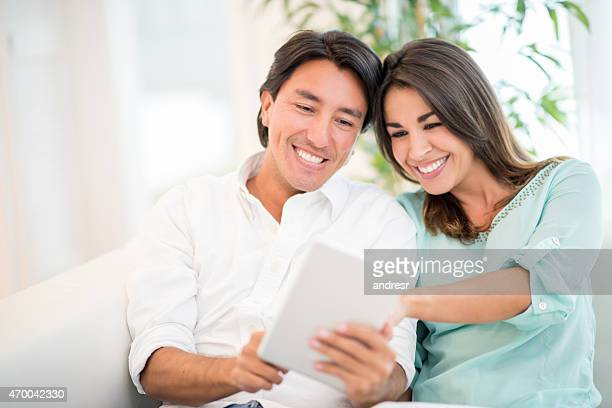 Couple using a tablet at home