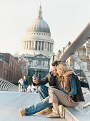 Couple Using a Video Phone to Photograph Themselves on the Millenium Bridge with St Pauls Cathedral in the Background