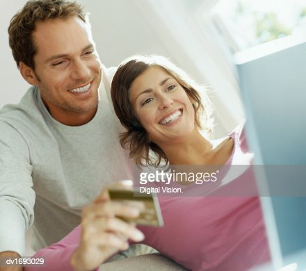 Couple Using Bank Card Online With a Laptop : Foto de stock