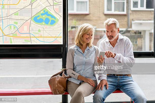 Couple using cell phone app at a bus station