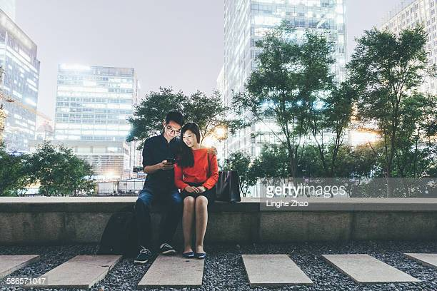 Couple using cell phone at night