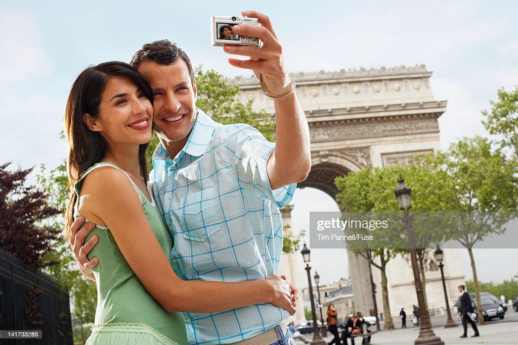 Couple Using Digital Camera Outside Arc de Triomphe