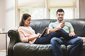 Couple using digital tablet and smartphone on sofa
