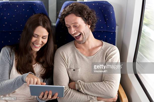 Couple using digital tablet in a train