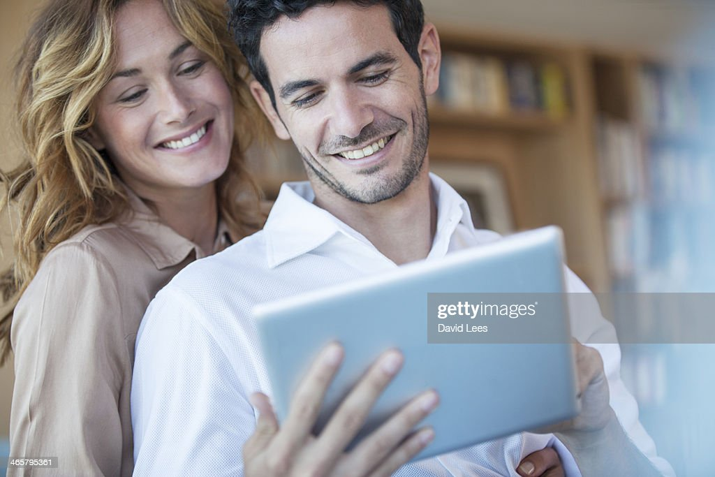 Couple using digital tablet in living room : Stock Photo