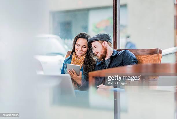 Couple using digital tablet in restaurant