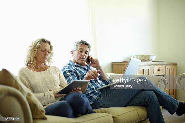 Couple using digital tablet, laptop and phone