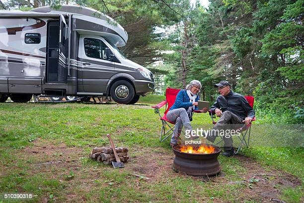 Couple using digital tablet near campfire