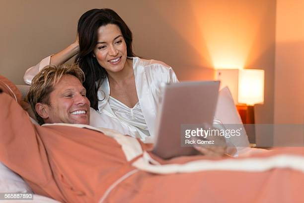 Couple using digital tablet on bed