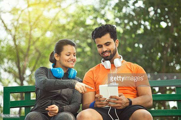 Couple using digital tablet on park bench