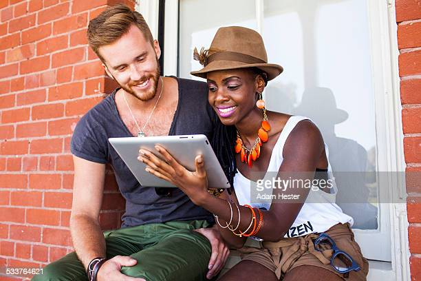 Couple using digital tablet outdoors