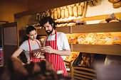 Couple using digital tablet in bakery shop
