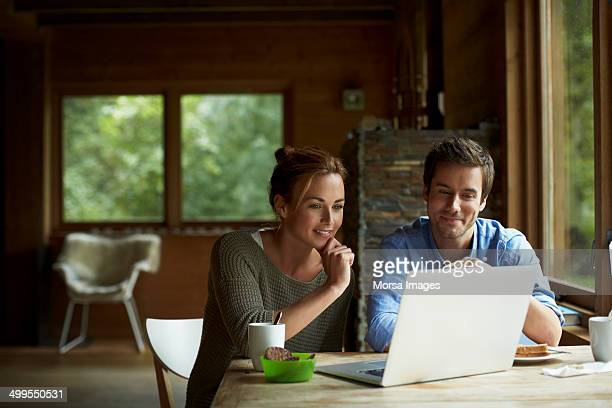 Couple using laptop at table in cottage