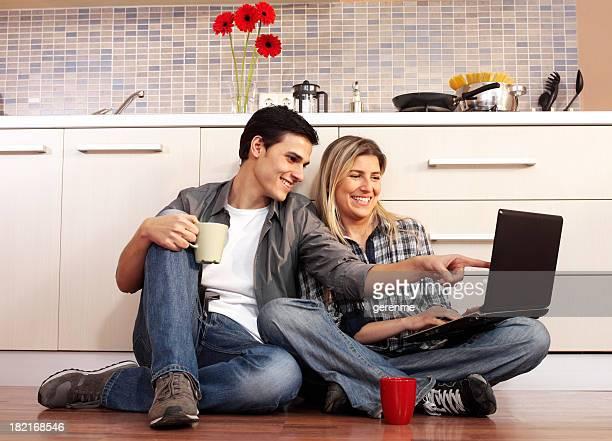 Casal usando computador portátil na cozinha