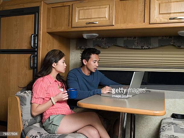Paar mit laptop in caravan
