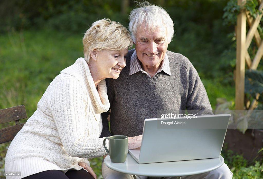 Couple using laptop in garden. : Stock Photo