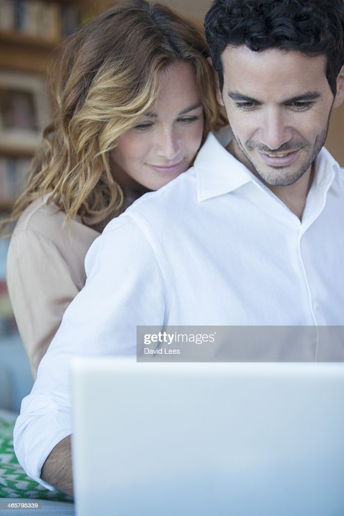 Couple using laptop in living room : Stock Photo