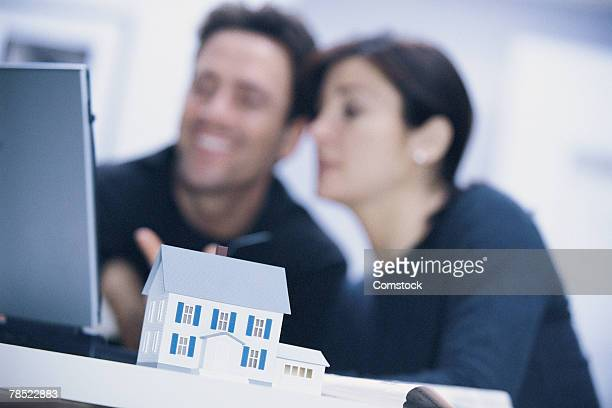 Couple using laptop , model house in foreground