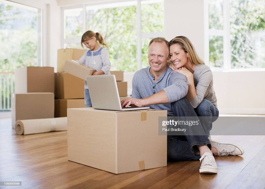 Couple using laptop on box in new house : Stock Photo
