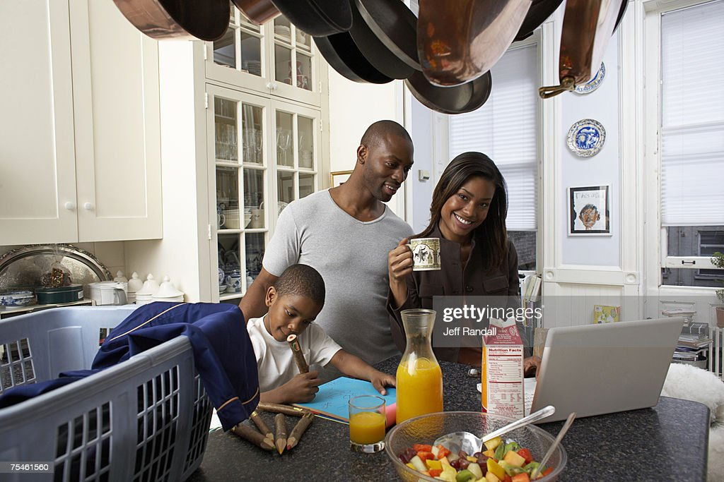 Couple using laptop on kitchen counter, son (6-7) drawing : Stock Photo
