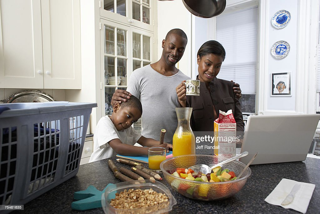 Couple Using Laptop On Kitchen Counter Son Drawing Stock Photo Getty Images