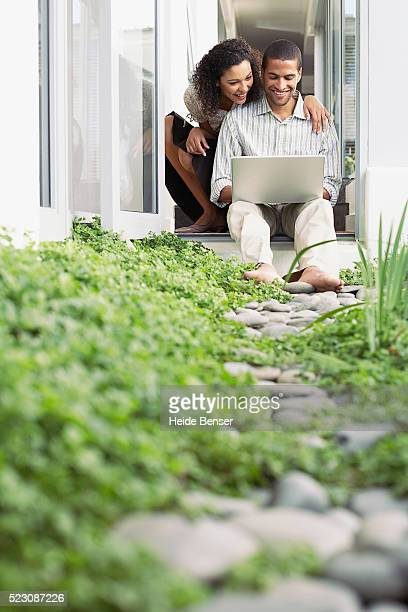 Couple using laptop on porch