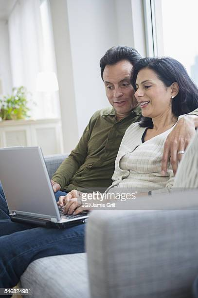 Couple using laptop on sofa in living room