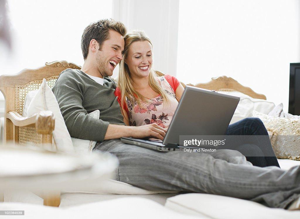 Couple using laptop on sofa : Stock Photo