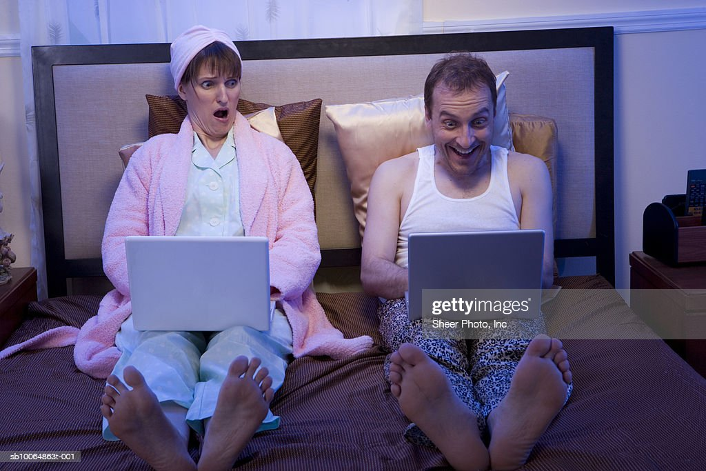 Couple using laptops side by side in bed : Stock Photo