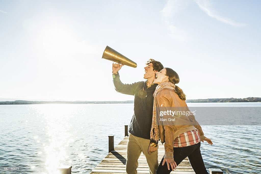 Couple using megaphone by lake