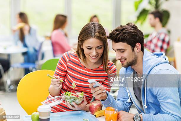 Couple using smart phone in cafeteria.