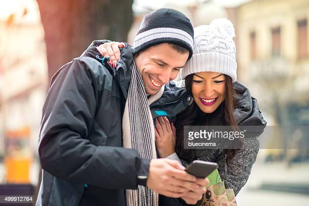 Couple Using Smart Phone On Street
