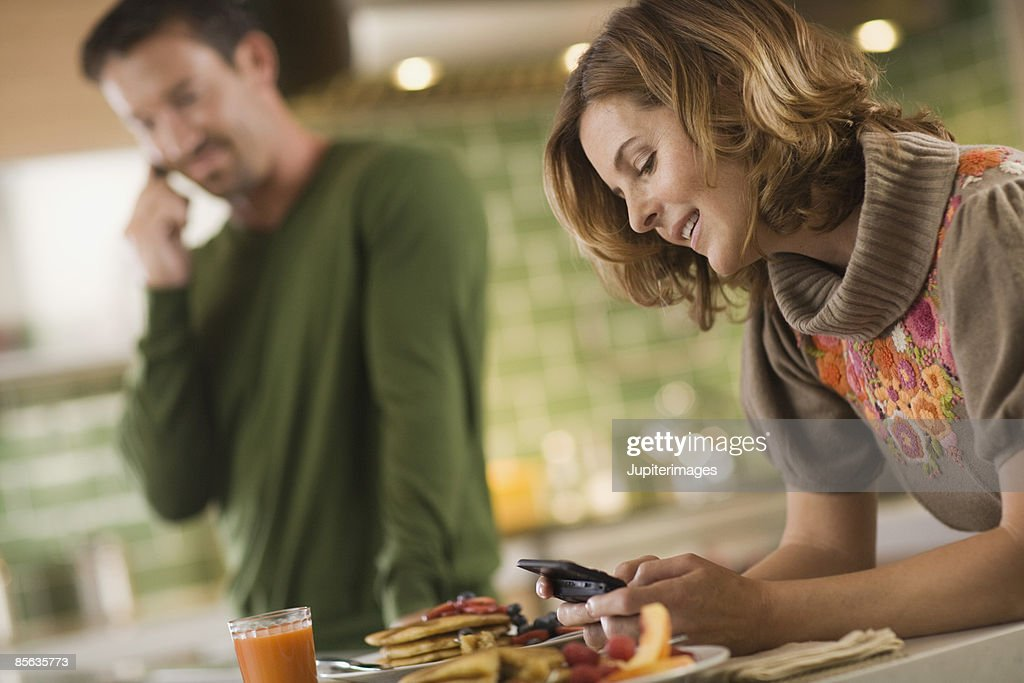 Couple using smartphone and cell phone at breakfast : Stock Photo