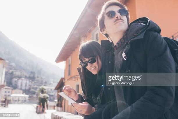 Couple using smartphone touchscreen, Monte San Primo, Italy