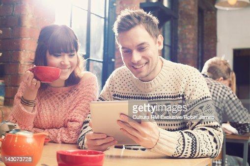 Couple using tablet computer in cafe : Bildbanksbilder
