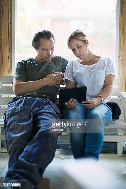 Couple using tablet computer in house being renovated