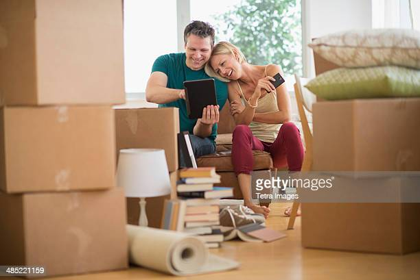 Couple using tablet pc in new home