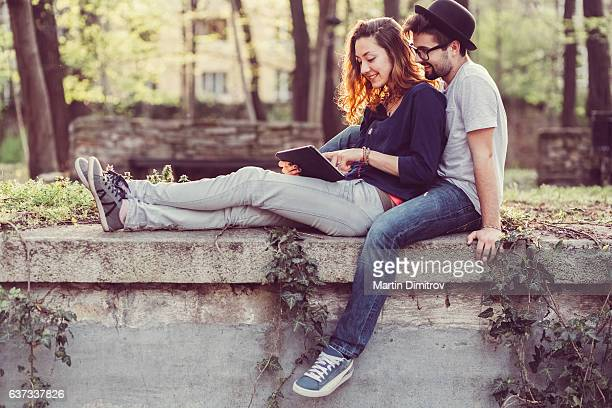 Couple using tablet pc in the park