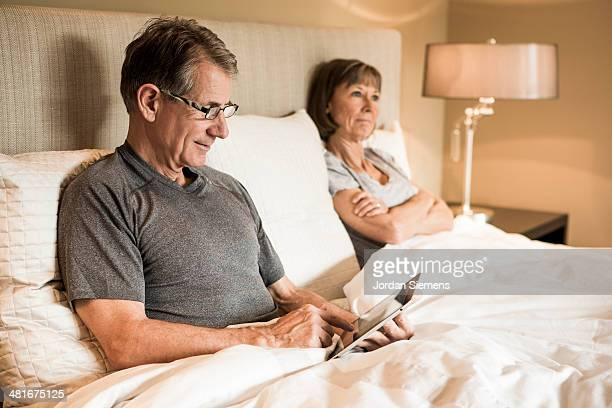Couple using technology in the bedroom.