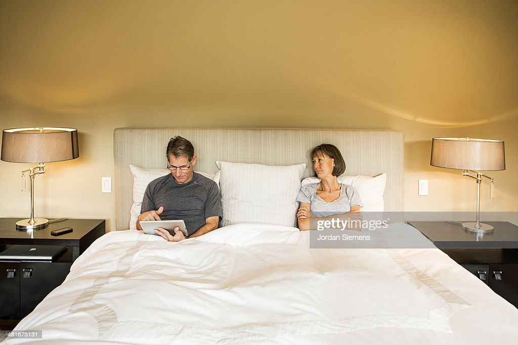 Couple using technology in the bedroom stock photo getty for Role playing ideas for couples in the bedroom